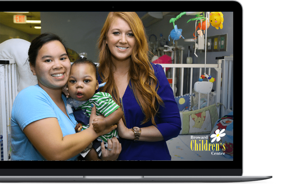 Image of two women and a child on a laptop screen