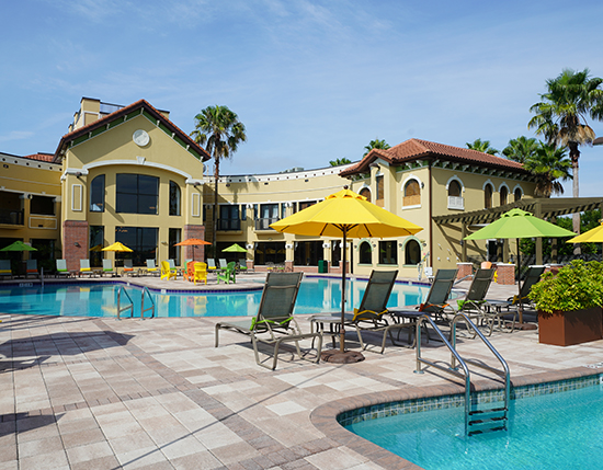 outdoor heated swimming pool and lap pool with colorful umbrellas and chairs, The Berkley, Orlando