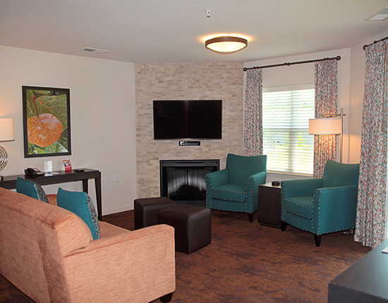 Guest suite living room areas featuring fireplace and window showing furnished balcony, The Colonies at Williamsburg