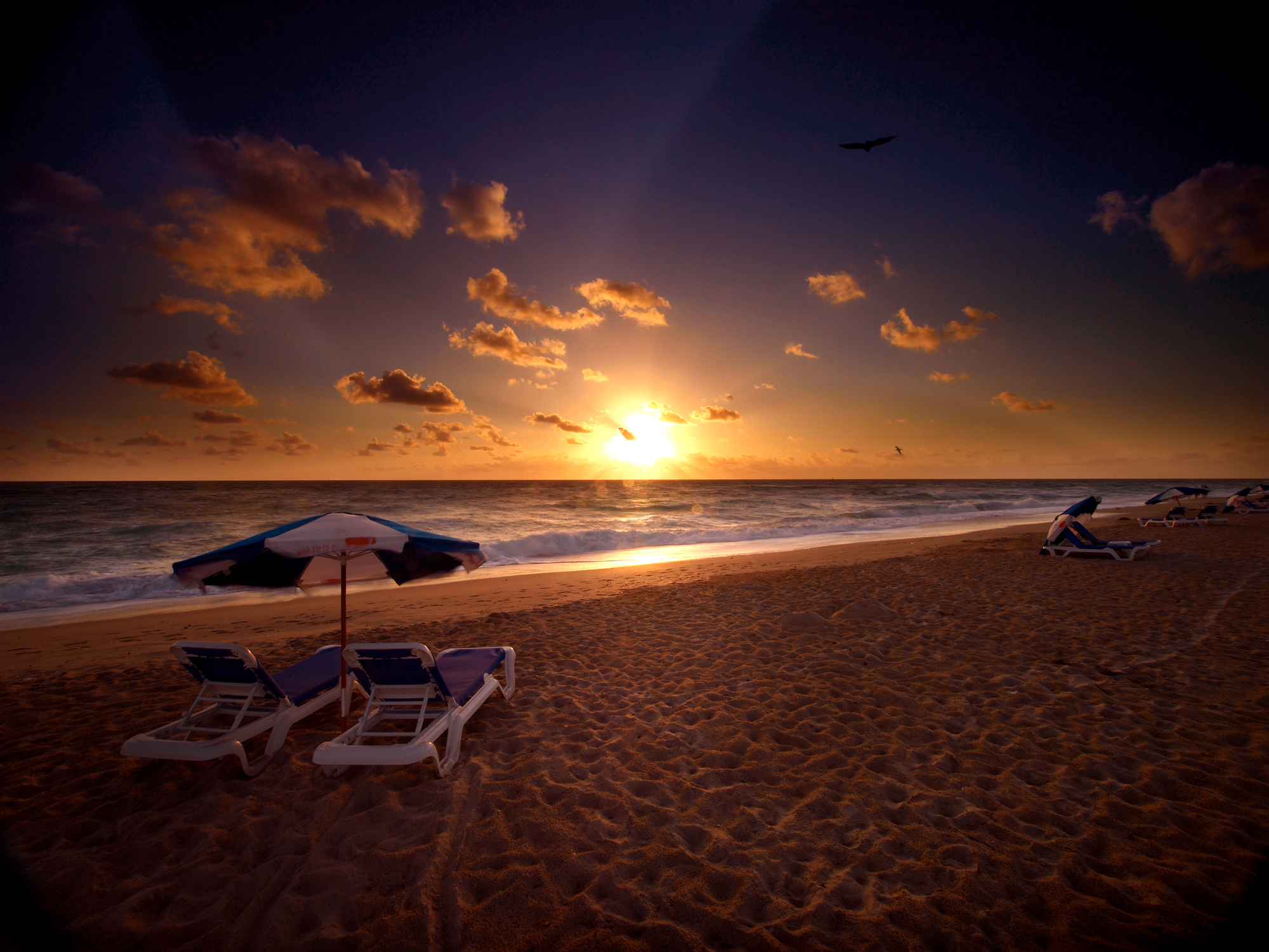 private beach area with rental umbrella and chairs at sunset, Palm Beach Shores Resort and Vacation Villas.