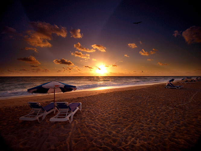 private beach area with rental umbrella and chairs at sunset, Palm Beach Shores Resort and Vacation Villas