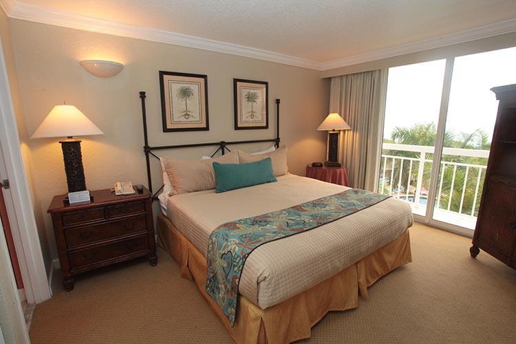guest suite bedroom with king size bed and glass doors leading to furnished outdoor balcony, Palm Beach Shores Resort and Vacation Villas