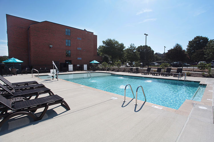outdoor swimming pool area with lounge chairs, Patriots Inn