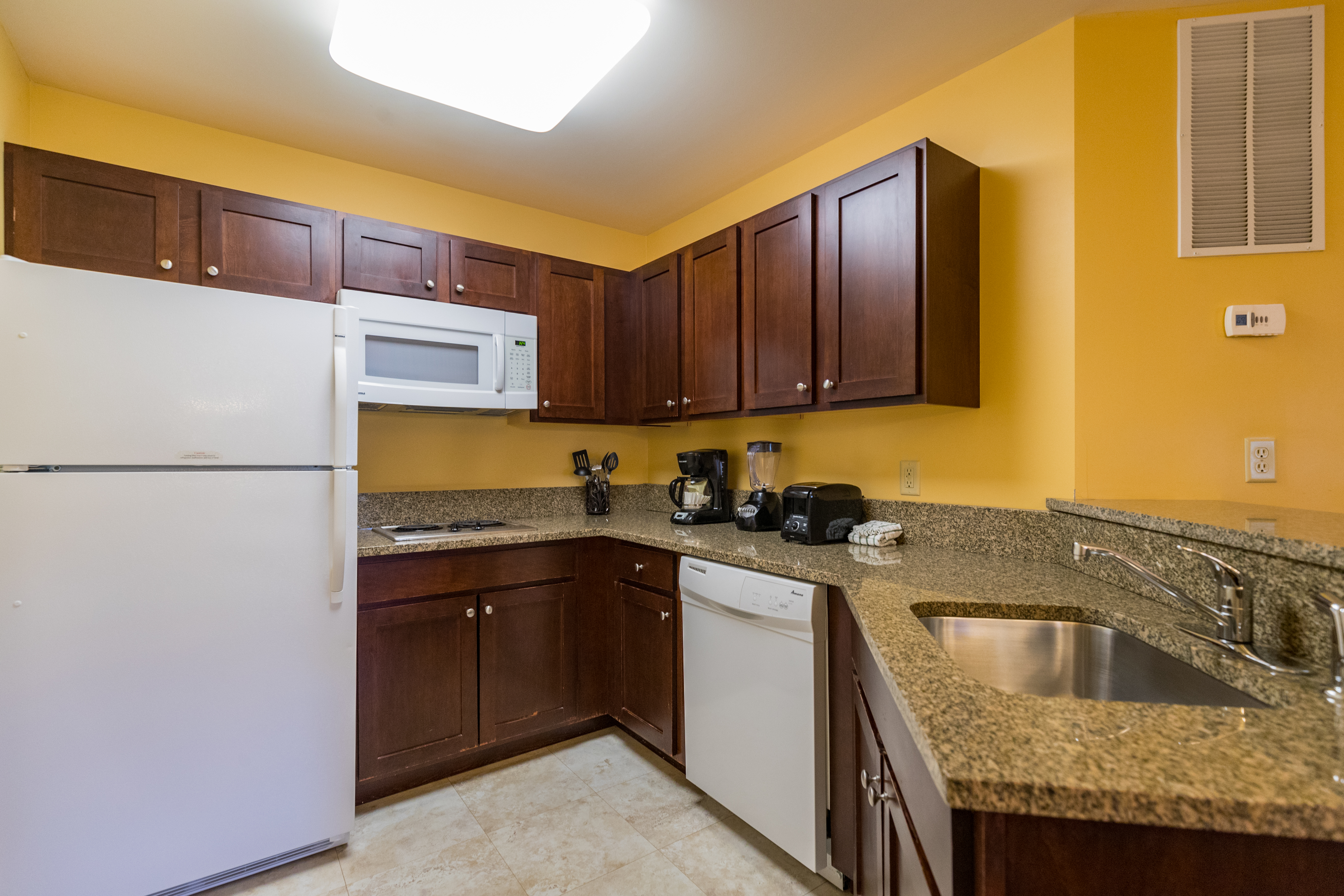 B Suite guest partial kitchen with granite counter tops and two burner cooktops, Vacation Village in the Berkshires