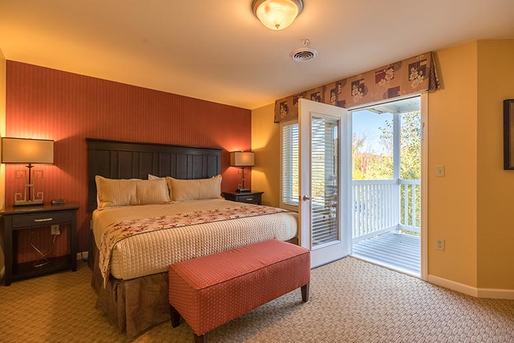 A Suite guest master bedroom with open door to furnished, private balcony, Vacation Village in the Berkshires