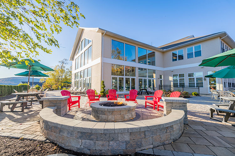 Outdoor fire pit with red Adirondack chairs, Vacation Village in the Berkshires