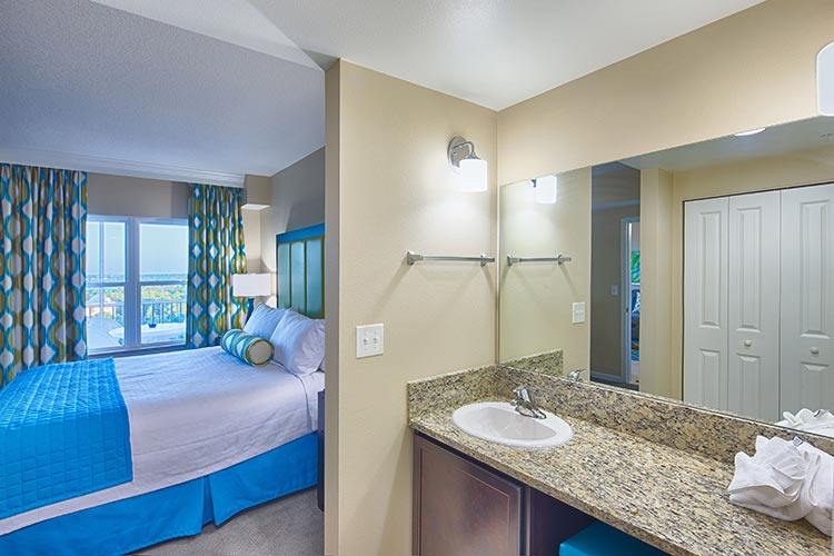guest master bedroom with master bathroom vanity in A Suite, Vacation Village at Parkway