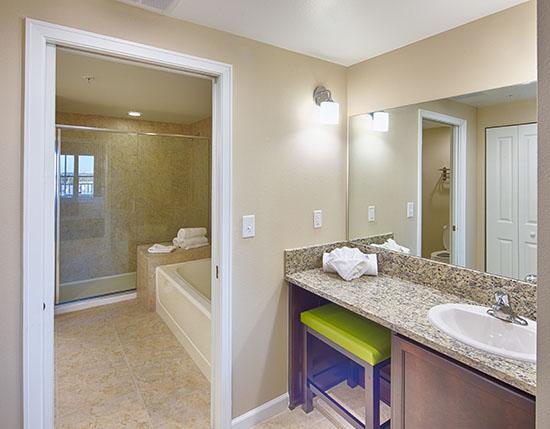 guest bedroom with separate vanity and bathroom sink in C Suite, Vacation Village at Parkway