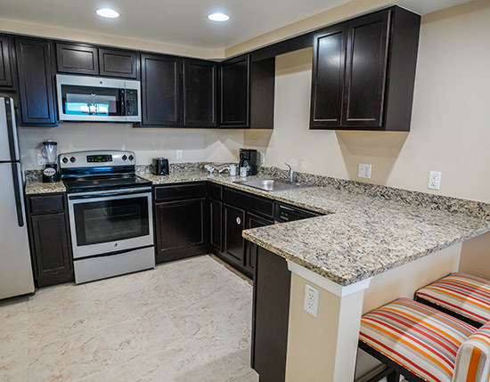guest full kitchen with granite countertops and bar stools in A Suite, Vacation Village at Parkway
