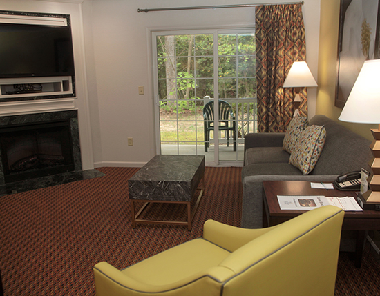 guest suite living room with fireplace and TV, Vacation Village at Williamsburg
